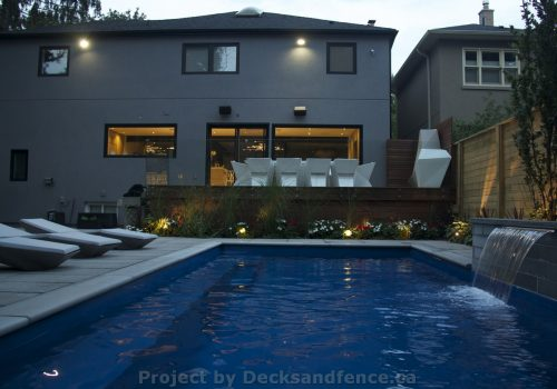 Complete landscaping project with deck outdoor kitchen and pool construction