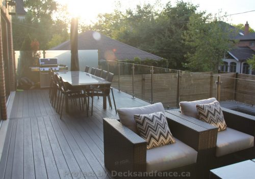 Large composite deck with glass railings and fence